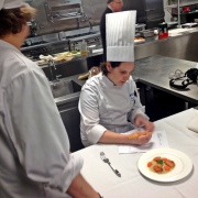 Chef Denise Perry evaluates a mid-term exam meal as a student looks on