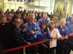 Ald. Sam Cahnman assists Store Manager Tom Moore With Thursday's Ribbon-Cutting At New Store