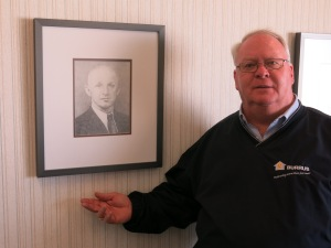 Tom Burrus with a photo of his grandfather, who started the seed company.  (Photo: Bill Wheelhouse/Harvest Public Media)